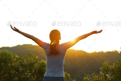 Young asian woman wellcome the sunrise on mountain top