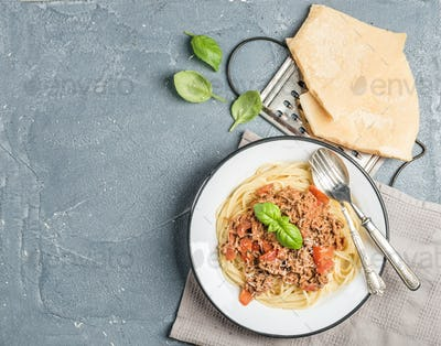 Pasta dinner. Spaghetti Bolognese in metal plate with Parmesan cheese