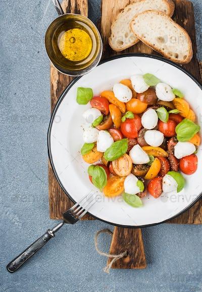 Italian Caprese salad with cherry tomatoes, small mozzarella and fresh basil