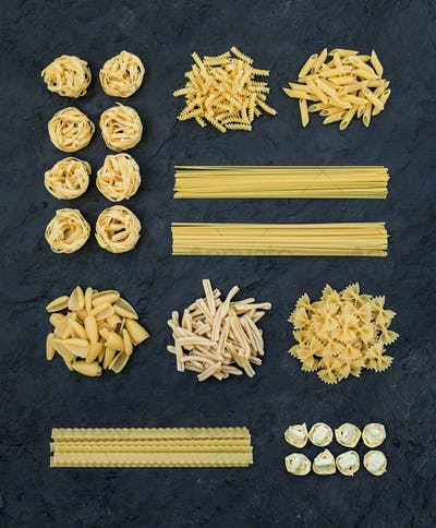 Different types of Italian uncooked pasta on black slate stone background, top view