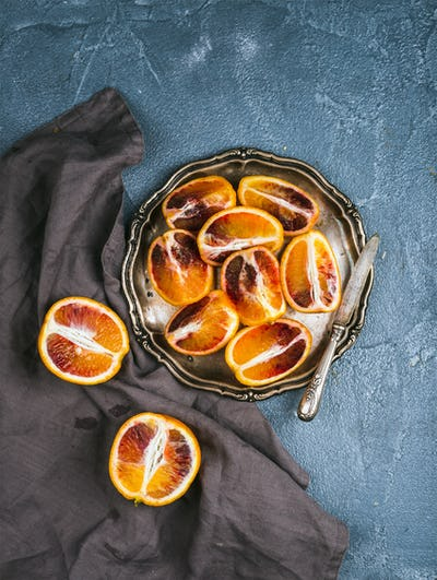 Bloody red sicilian oranges cut into quarters in vintage metal plate