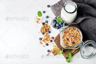Healthy breakfast ingrediens. Homemade granola in open glass jar, milk or yogurt bottle