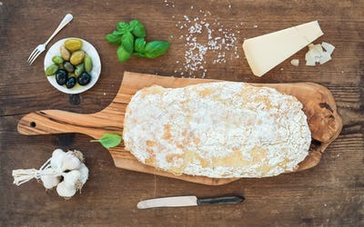 Freshly baked ciabatta bread with garlic, mediterranean olives, basil and Parmesan cheese