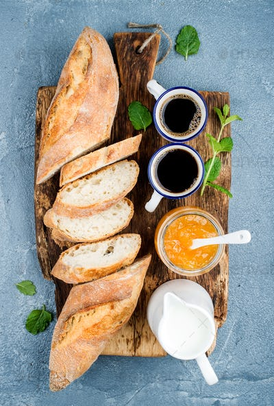 Breakfast set. Baguette, orange jam and coffee in cups on rustic wooden board