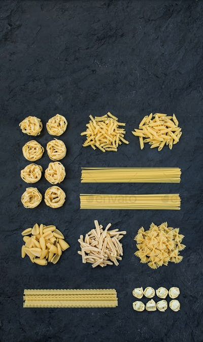 Different types of Italian uncooked pasta on black slate stone background