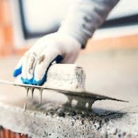 construction worker using steel trowel for plastering