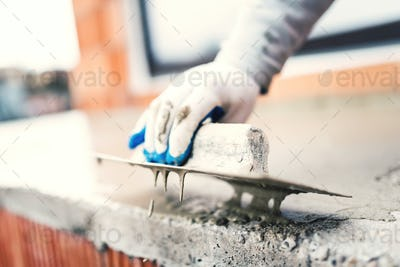 construction worker using steel trowel for plastering