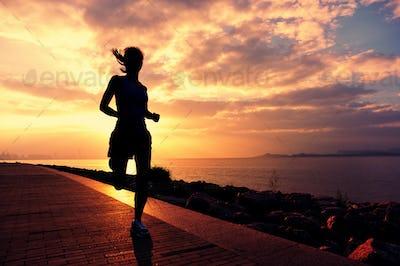 Sporty fitness woman running on sunrise seaside trail