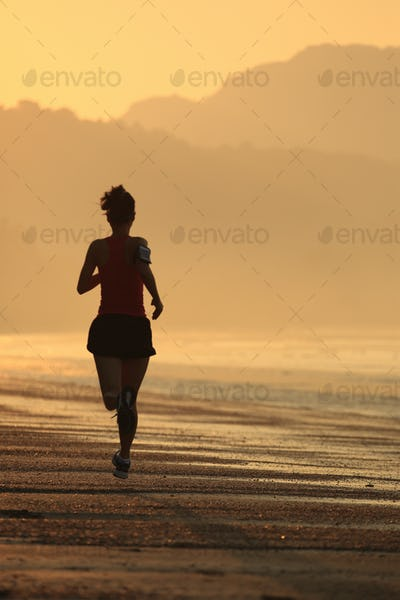 Sporty fitness woman running on sunrise beach