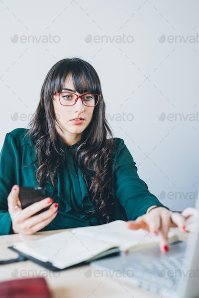 Young beautiful caucasian businesswoman sitting on a desk, using