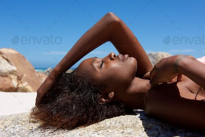 Beautiful young female model lying on rock