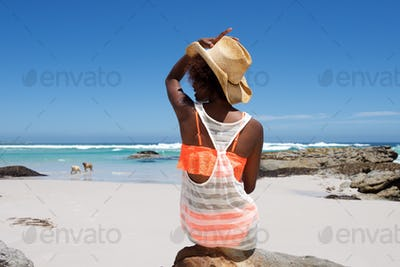 Young woman sitting on beach with a hat