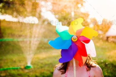 Beautiful girl in swimsuit hiding behind pinwheel, summer garden