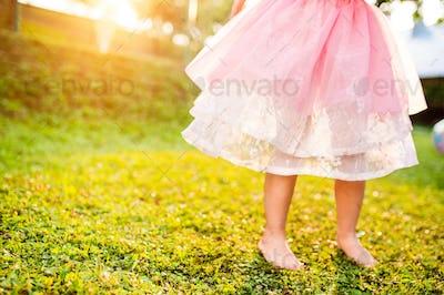 Unrecognizable girl in princess skirt running in sunny garden