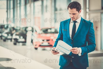 Confident young car dealer standing in showroom.
