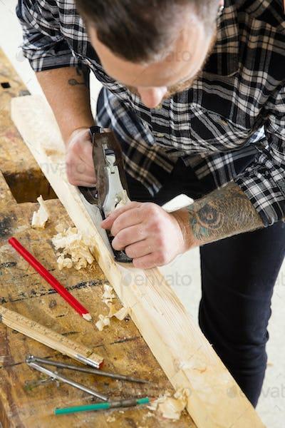 Focused craftsman working with plane on wood plank in workshop