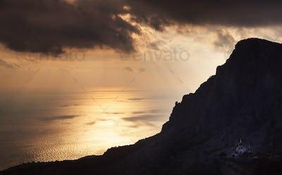 Church under a mountain at sunset