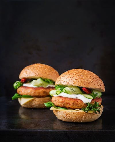 Big sandwich - hamburger with juicy chicken and tartar sauce on black background