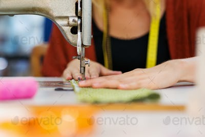 Hands of unrecognizable tailor woman working with sewing machine