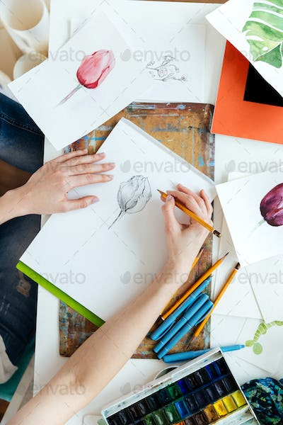 Woman painter drawing tulips by gel ink pen at table