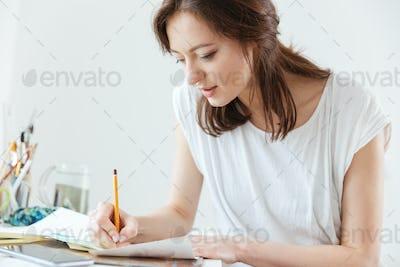 Woman artist making sketches in workshop