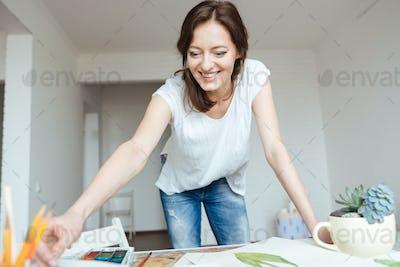 Happy woman painter working in art studio