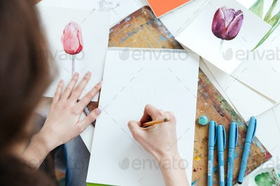 Woman painter sitting and drawing by pencil at the table