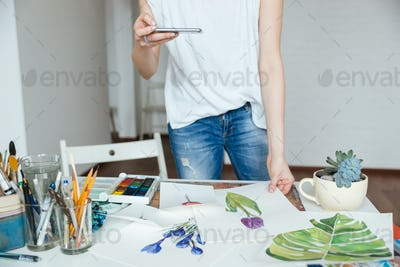 Woman artist taking photos of her drawings using smartphone
