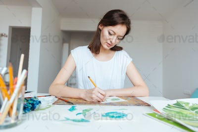 Concentrated woman painter making sketches with pencil in art studio