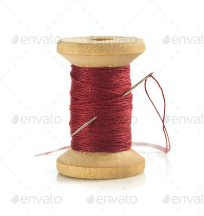 spool of thread and needle on white