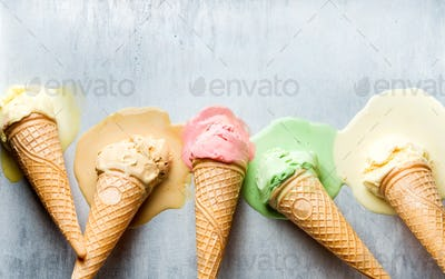 Colorful ice cream cones of different flavors. Melting scoops. Top view,  steel metal background