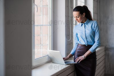 Young successful happy smiling business woman on laptop