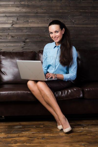 Happy brunette sitting on sofa in living room using laptop