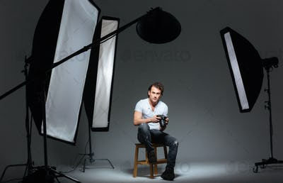 Man photograph sitting on the chair in professinal studio