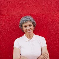 Happy senior woman standing against red background