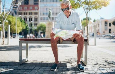 Senior tourist reading a city map