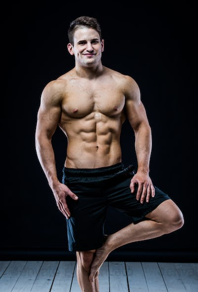 Strong Athletic Man baalncing on the one leg. Dark background.