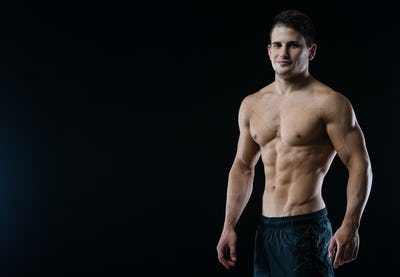 Young and fit male model posing his muscles looking straight to camera