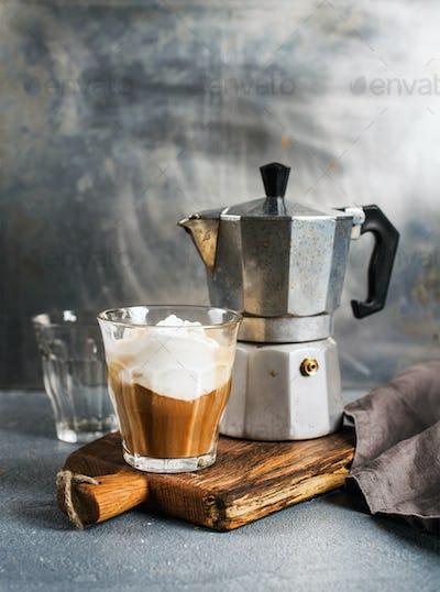 Glass of coffee with ice cream on rustic wooden board and steel Italian Moka pot
