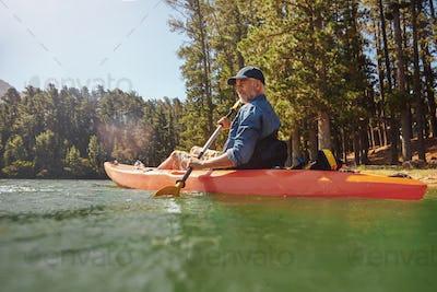 Mature man with kayak in a lake
