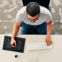 Designer using digital graphics tablet and desktop
