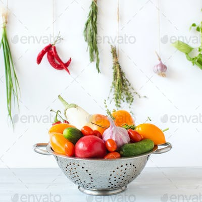 Fresh vegetables in a colander on a wooden.