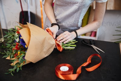 Woman florist making bouquet of flowers using red ribbon
