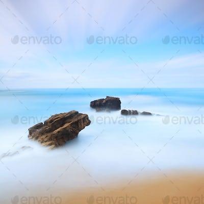 Three rocks seascape. Long exposure photography.