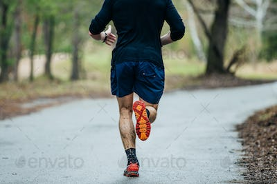 young male runner running on road