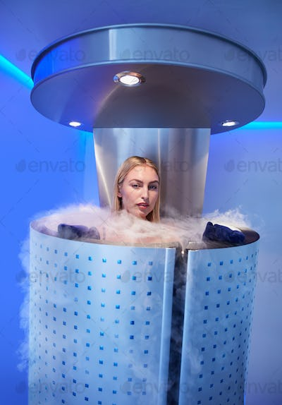 Beautiful woman in a full body cryotherapy camber