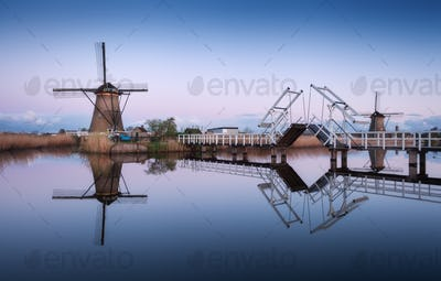 Landscape with traditional dutch windmills and drawbridge at sun