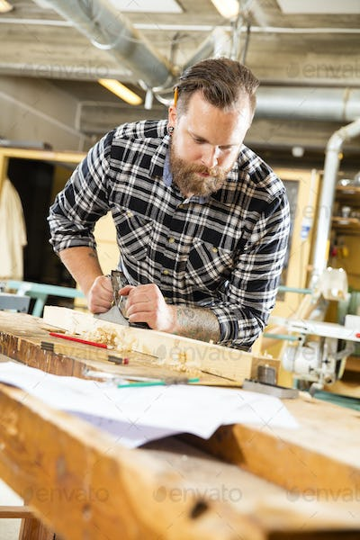 Carpenter work with plane on wood plank in workshop