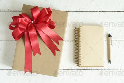 Gift box with red ribbon on white wooden background