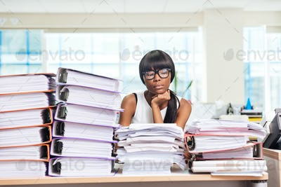 Businesswoman sitting at the table with many work in office